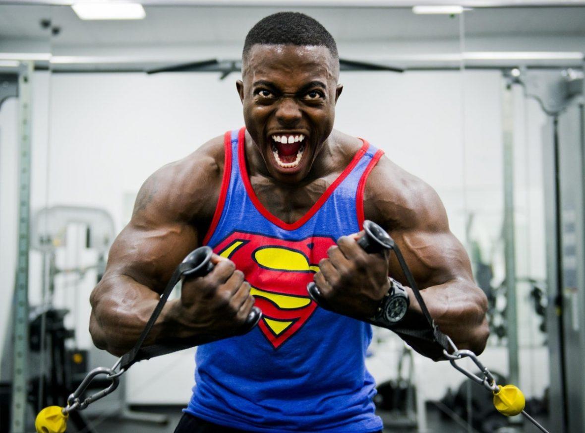 Bodybuilder in un superman con le migliori prestazioni per l'ipertrofia lavora con i moschettoni